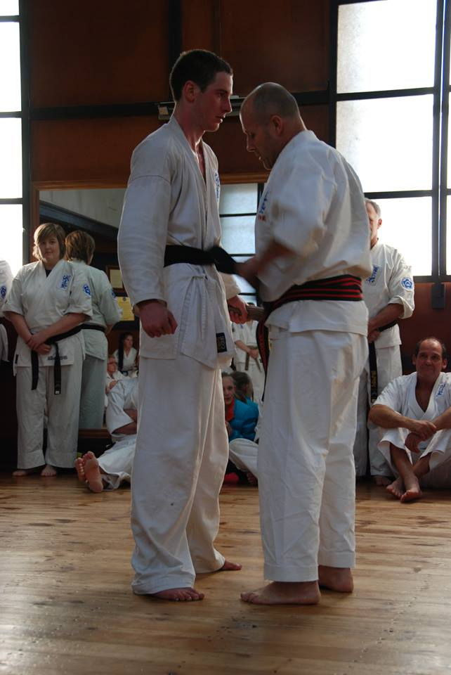 Chris receiving his belt from Jun Shihan Kelvin Lewis